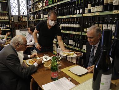 Pramusaji melayani pelanggan di dalam restoran di pusat kota Roma, Italia, Senin (1/6/2021). Mulai Selasa, pelanggan kembali diizinkan mengakses bar dan restoran, yang sebelumnya hanya diizinkan untuk melayani makan di luar ruangan atau takeaway karena pembatasan Covid-19. (AP Photo/Gregorio Borgia)