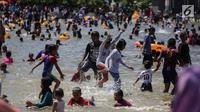 Sejumlah anak bermain air di pantai Ancol, Jakarta, Senin (25/12). Pengunjung lebih memilih liburan ke Pantai Ancol karena gratis, tidak dikenai biaya tambahan. (Liputan6.com/Faizal Fanani)