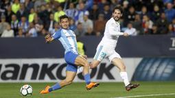 Pemain Real Madrid, Isco (kanan) melepaskan tembakan melewati adangan pemain Malaga, Roberto Jose Rosales pada lanjutan La Liga Santander di Rosaleda stadium, Malaga, (15/4/2018). Madrid menang 2-1. (AP/Miguel Morenatti)