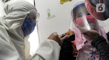 Dokter dengan Alat Pelindung Diri memberikan vaksin radang otak pada anak di Rumah Vaksinasi Sawangan, Depok, Selasa (16/6/2020). Orang tua diminta tidak menunda pemberian imunisasi pada anak-anak yang masih harus menerima imunisasi lengkap di tengah pandemi Covid-19. (merdeka.com/Arie Basuki)