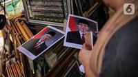 Poster Presiden Joko Widodo dan Wakil Presiden terpilih Ma'ruf Amin yang dijualnya di Pasar Baru, Jakarta, Rabu (16/10/2019). Harga bingkai foto Presiden dan Wakil Presiden tersebut dijual mulai dari harga Rp 90 ribu. (Liputan6.com/Faizal Fanani)