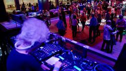 Pengunjung berjoged saat DJ Wika Szmyt memainkan musik di sebuah klub di Warsawa, Polandia, Senin (25/3). Di usianya yang menginjak 80 tahun, Wika masih aktif menghibur di salah satu klub di Warsawa. (REUTERS/Kacper Pempel)