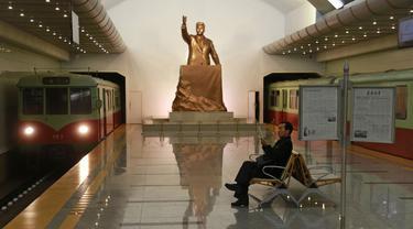 Seorang pria membaca sambil menunggu kereta dengan latar belakang patung mendiang Presiden Korea Utara Kim Il Sung di stasiun kereta bawah tanah Kaeson di Pyongyang, Korea Utara (23/11/2019). Stasiun Kaeson adalah stasiun di Jalur Chŏllima Metro Pyongyang. (AP Photo/Dita Alangkara)