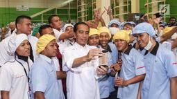 Presiden Jokowi bersama karyawan saat berswafoto di pabrik Mayora di Cikupa Tangerang, Senin (18/2). Presiden Jokowi secara resmi melepas kontainer ekspor ke 250.000 ke Filipina dan memperingati HUT Mayora Group yang ke 42. (Liputan6.com/Fery Pradolo)