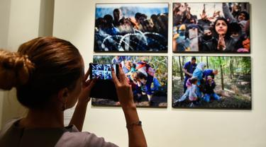 """Pengunjung mengambil foto saat pameran karya fotografer Agence France-Presse (AFP) mengenai krisis migrasi di Eropa di pusat seni Bozar di Brussels (3/5). Pameran ini berjudul """"Puting a Face on the Invisibles. (AFP Photo/John Thys)"""