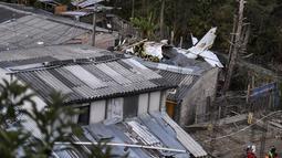 Tim penyelamat berada di lokasi jatuhnya pesawat kecil di tengah-tengah rumah penduduk di Popayan, Kolombia, Minggu (15/9/2019). Otoritas setempat sedang menyelidiki penyebab dari kecelakaan pesawat yang jatuh beberapa menit setelah lepas landas dari bandara Popayan. (Luis ROBAYO / AFP)