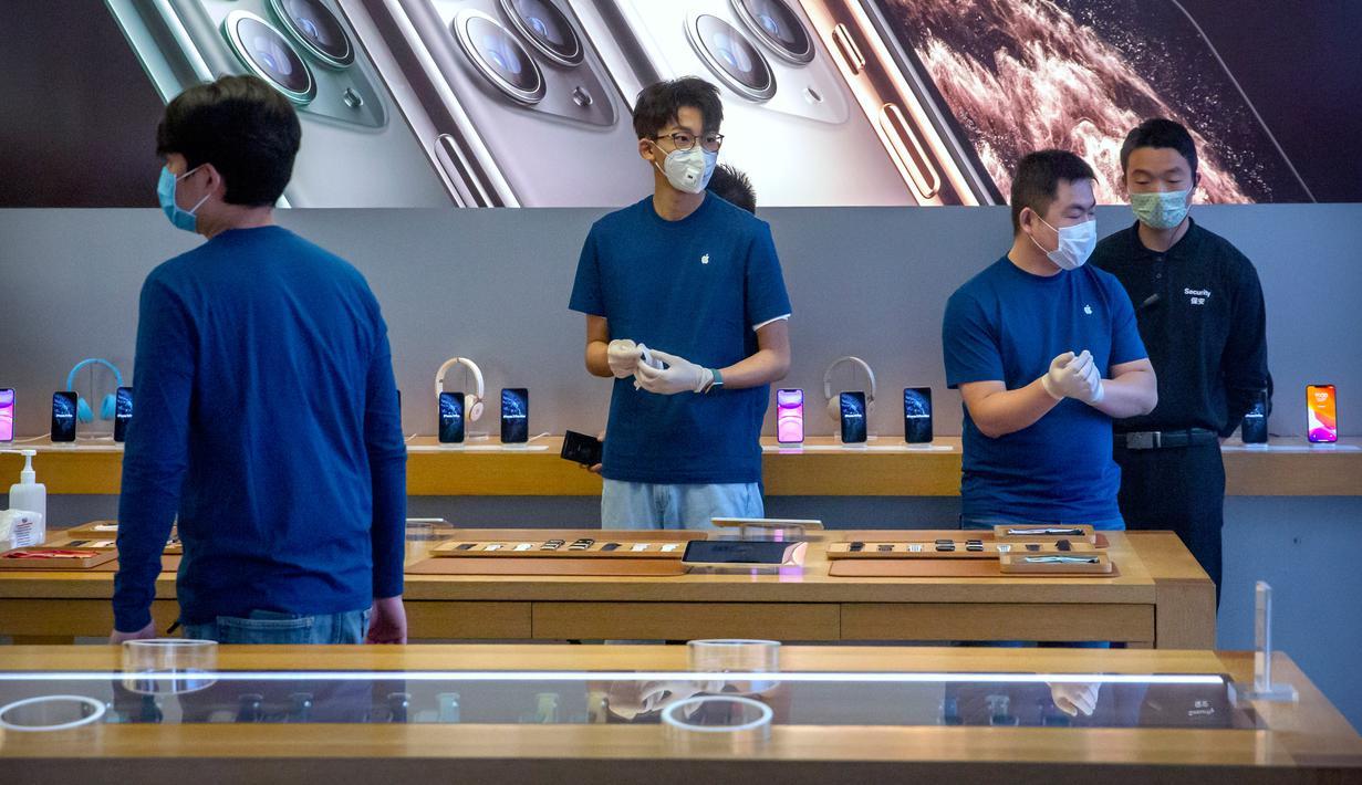 Para pekerja mengenakan masker saat menjaga Apple Store yang dibuka kembali di Beijing, China, Jumat (14/2/2020). Apple kembali membuka tokonya di China setelah pada awal Februari lalu menutup seluruhnya karena khawatir terhadap wabah virus corona. (AP Photo/Mark Schiefelbein)