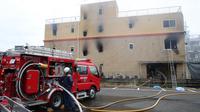 Petugas pemadam kebakaran melihat ke arah studio animasi Kyoto Animation di Kyoto, Jepang, Kamis (18/7/2019). Sebagian besar muka bangunan berubah menjadi hitam karena hangus terbakar. (JIJI PRESS/AFP)