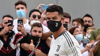 Striker Juventus, Cristiano Ronaldo disambut penggemar setibanya di  gedung pusat medis Juventus di Turin, Italia, Senin (26/7/2021). Cristiano Ronaldo menjalani tes medis menjelang musim keempatnya bersama klub Seria A itu. (Miguel MEDINA/AFP)