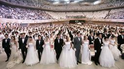 Pasangan pengantin menghadiri pernikahan massal di Cheong Shim Peace World Center, Gapyeong, Korea Selatan, Senin (27/8). Acara ini diikuti oleh pasangan pengantin dari seluruh dunia. (AP Photo/Ahn Young-joon)