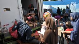 Warga membeli kebutuhan pokok menggunakan KJP saat berlangsungnya Program Pangan Murah di RPTRA Utakara Beriman, Jakarta, Kamis (20/6/2019). Kebutuhan Pokok dalam Program Pangan Murah tersebut terdiri atas beras, telur, daging sapi, daging ayam, ikan, dan susu. (merdeka.com/Iqbal S Nugroho)