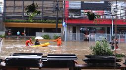 Petugas mengevakuasi warga menggunakan perahu karet saat melintasi banjir yang merendam kawasan Benhil, Jakarta, Selasa (25/2/2020). Hujan yang mengguyur wilayah tersebut membuat air sungai meluap sehingga menyebabkan Banjir setinggi pinggang orang dewasa. (Liputan6.com/Angga Yuniar)