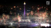 Kembang api menghiasi malam pergantian tahun baru 2018 di kawasan silang Monumen Nasional (Monas), Jakarta, Senin (1/1/2018). Monas menjadi salah satu lokasi pilihan Warga Jakarta untuk merayakan malam pergantian tahun. (Liputan6.com/Johan Tallo)