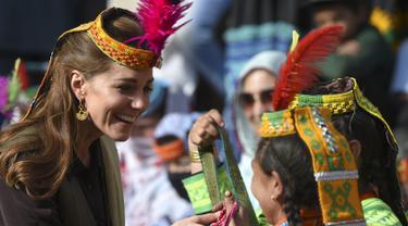 Duchess of Cambridge, Kate Middleton mengenakan topi tradisional suku Kalash tersenyum saat menerima hadiah dari seorang anggota suku Kalash selama kunjungannya ke Lembah Bumburate di Distrik Chitral utara Pakistan (16/10/2019). (AFP Photo/Farooq Naeem)