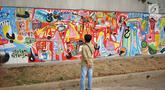 Warga melihat mural yang menghiasi tembok dalam acara Mural Cikini Project #1 di Taman Plaza Teater Besar, Taman Ismail Marzuki, Jakarta, Jumat (23/8/2019). Project #1/Mural Cikini yang diikuti oleh 4 seniman digelar dalam rangka menata estetika ruang publik. (Liputan6.com/Faizal Fanani)
