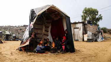 Warga Palestina menghangatkan diri di sekitar api tungku di area permukiman kumuh sebuah kamp pengungsi saat cuaca badai di Kota Khan Younis, Jalur Gaza selatan, pada 26 November 2020. (Xinhua/Yasser Qudih)