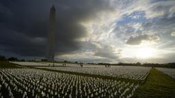 Warga melihat bendera putih untuk mengenang orang AS yang meninggal karena COVID-19 dalam instalasi seni sementara seniman Suzanne Brennan Firstenberg 'Di Amerika: Ingat' di National Mall, Washington, AS, Jumat (17/9/2021). Instalasi terdiri dari lebih dari 630.000 bendera. (AP Photo/Brynn Anderson)