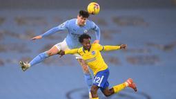 Bek Manchester City, John Stones (atas) memenangi duel udara dengan striker Brighton and Hove Albion, Percy Tau dalam laga lanjutan Liga Inggris 2020/21 di Etihad Stadium, Rabu (13/1/2021). Manchester City menang 1-0 atas Brighton. (AFP/Laurence Griffiths/Pool)