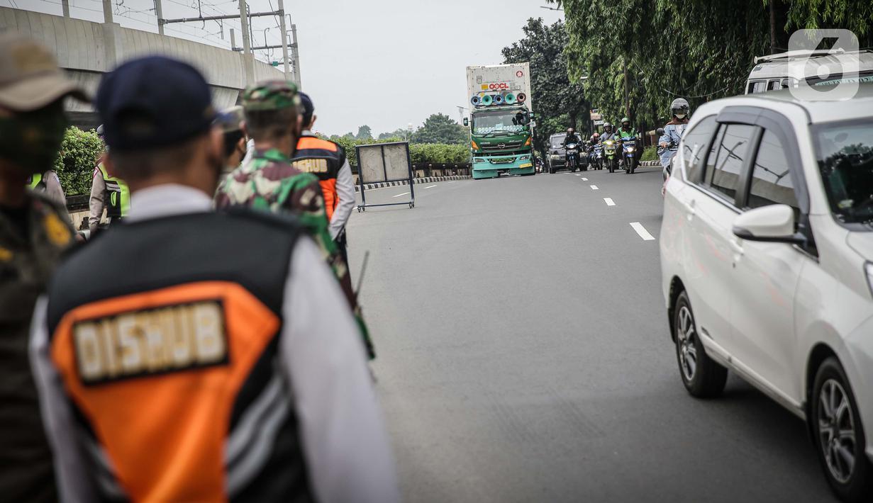 Petugas mengawasi kendaraan yang melintasi pos cekpoin penyekataan arus mudik di kawasan Pasar Jumat, Kamis (6/5/2021). Penyekatan dan cek poin dilakukan saat penerapan larangan mudik Lebaran 2021 sebagai upaya pencegahan penularan COVID-19. (Liputan6.com/Faizal Fanani)