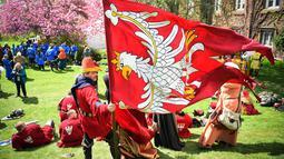 Seorang peserta memegang bendera timnya saat mengikuti kompetisi IMCF di Scone Palace, Perthshire, Skotlandia (10/5). Mereka bergaya dan menggunakan senjata yang dulu digunakan para kesatria untuk bertempur.  (AFP/Andy Buchanan)