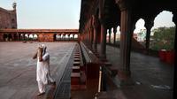 Seorang Muslim menyeka usai berwudhu sebelum salat pada hari pertama bulan puasa Ramadan di Masjid Jama yang sepi, yang biasanya dipadati ribuan umat, selama penguncian nasional untuk mengendalikan penyebaran virus corona Covid-19, di New Delhi, India (25/4/2020). (AP Photo/Manish Swarup)