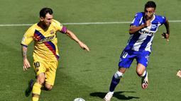 Pemain Barcelona Lionel Messi (kiri) berebut bola dengan pemain Alaves Victor Camarasa pada pertandingan La Liga di Stadion Mendizorroza, Vitoria, Spanyol, Minggu (19/7/2020). Barcelona menang 5-0. (AP Photo/Alvaro Barrientos)