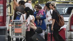 Para migran bersiap naik bus selama operasi polisi di pusat Athena, Yunani (19/9/2019). Polisi di Athena pada 19 September 2019 memindahkan lebih dari 200 migran, termasuk lusinan anak-anak, dari dua tempat di pusat kota sebagai bagian dari pembersihan. (AFP Photo/Louisa Gouliamaki)
