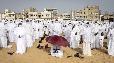 Pengikut komunitas Layene Senegal terlihat selama perayaan Tabaski (Idul Adha) di lingkungan populer Yoff di Dakar, Rabu (21/7/2021). Para jemaah mengenakan pakaian putih untuk merayakan hari raya umat Muslim yang dikenal di Senegal sebagai 'Tabaski'. (JOHN WESSELS / AFP)