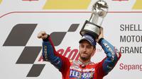 Pebalap Ducati, Andrea Dovizioso, melakukan selebrasi usai menjuarai balapan MotoGP Malaysia di Sirkuit Sepang, Minggu (29/10/2017). Dovizioso finis pertama dengan catatan waktu 44 menit 51,497 detik. (AP/Vincent Thian)