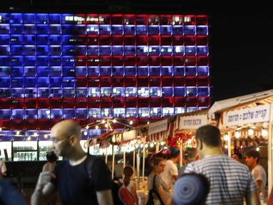 Warga melintas di dekat balai kota Tel Aviv yang dihiasi warna bendera AS untuk menghormati korban penembakan brutal di Las Vegas di Rabin Square, Tel Aviv (2/10). Pelaku penembakan diketahui bernama Stephen Paddock 64 tahun. (AFP Photo/Jack Guez)
