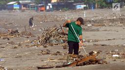 Seorang sukarelawan membersihkan sampah di kawasan Pantai Citepus, Pelabuhan Ratu, Sukabumi, Jumat (4/1). Kegiatan aksi Jumsih (Jumat Bersih) setiap minggunya ini sudah berlangsung sejak tahun 2002. (Merdeka.com/Arie Basuki)