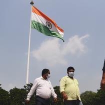 Sejumlah pria mengenakan masker berjalan melewati bendera nasional India di New Delhi (16/9/2020). Total kasus Covid-19 di India melampaui lima juta pada 16 September, data kementerian kesehatan menunjukkan Pandemi meluas cengkeramannya di negara tersebut. (AFP/Sajjad Hussan)