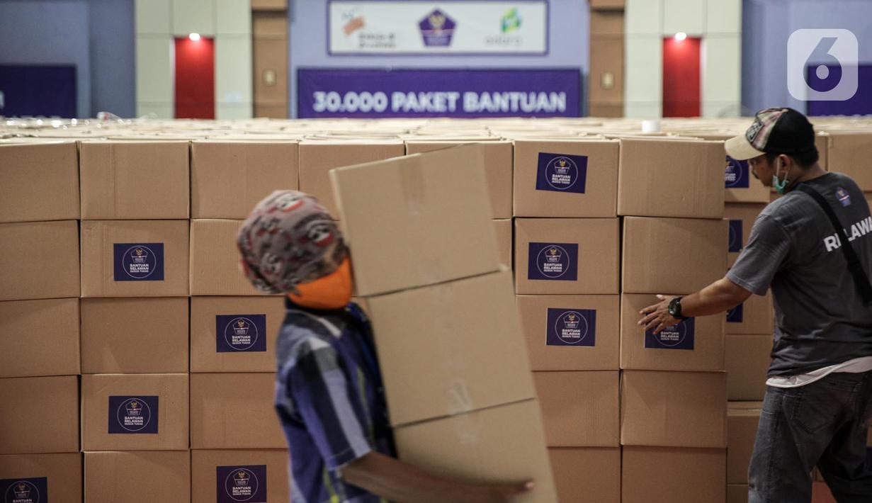 Relawan Gugus Tugas Percepatan Penanganan COVID-19 memindahkan kotak berisi sembako di GOR Gelanggang Remaja, Jakarta, Senin (18/5/2020). Relawan Gugus Tugas Percepatan Penanganan COVID-19 membagikan 30.000 paket bantuan kepada warga Jabodetabek yang terdampak COVID-19. (Liputan6.om/Faizal Fanani)
