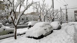 Salju tebal menutupi mobil yang terparkir di Ibu Kota Teheran, Iran, Minggu (28/1). Menurut kantor berita resmi Iran, IRNA, sejumlah daerah pegunungan menerima salju setinggi 1,3 meter (lebih dari empat kaki). (AFP PHOTO/ATTA KENALI)
