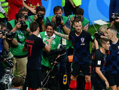 Mario Mandzukic (kiri) dan Ivan Rakitic menyapa fotografer AFP, Yuri Cortez (tengah) usai merayakan gol pada semifinal Piala Dunia 2018 di Luzhniki Stadium, Moskow, (11/7/2018). Yuri jatuh saat perayaan gol skuat Vatreni. (AFP/Mladen Antonov)