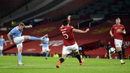Gelandang Manchester City, Kevin De Bruyne, melepaskan tendangan ke gawang Manchester United pada laga Piala Liga Inggris di Stadion Old Trafford, Rabu (6/1/2021). City menang dengan skor 2-0. (Peter Powell/Pool via AP)