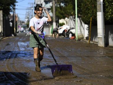 Seorang anak membersihkan lumpur dari jalan setelah banjir surut di Kawasaki, Minggu (13/10/2019). Topan dahsyat Hagibis yang menerjang sejumlah wilayah di Jepang menyebabkan banjir di beberapa lokasi. (Photo by WILLIAM WEST / AFP)