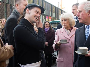 Pangeran Charles bersama istrinya, Duchess of Cornwall Camilla menikmati teh sambil berbincang ketika mengunjungi Swiss Cottage Farmers Market di London utara, Rabu (6/11/2019). Kunjungan Charles dan Camila untuk mengucapkan selamat dan memperingati ulang tahun ke-20 pasar tersebut. (Eddie Mulhollan