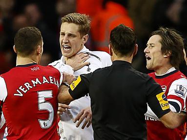 Bek Arsenal, Thomas Vermaelen beradu argumen dengan pemain Tottenham, Michael Dawson pada laga Liga Premier di Stadion White Hart Lane, Inggris, Minggu (3/3/2013). (EPA/Kerim Okten)
