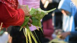 Pedagang dan pembeli bertransaksi kulit cangkang ketupat di Pasar Peterongan Semarang, Jawa Tengah, Kamis (12/6). Warga membeli kulit ketupat yang dijual Rp 12.000 per ikat itu untuk melengkapi aneka masakan khas Lebaran. (Liputan6.com/Gholib)