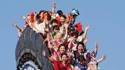 Para wanita berpakaian Kimono bermain roller coaster selama Hari Kedewasaan di Tokyo (14/1). Hari Kedewasaan dimana siapa saja yang baru menginjak usia 20 tahun diperbolehkan merokok, mengonsumsi alkohol, dan mengikuti Pemilu. (AP Photo/Koji Sasahara)