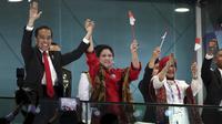Presiden Republik Indonesia, Joko Widodo, bersama ibu negara, Iriana Widodo, menyapa penonton saat pembukaan Asian Games 2018, Sabtu (18/8/2018). (AP/Dita Alangakara)