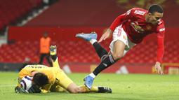 Penyerang Manchester United, Mason Greenwood, terjatuh saat berebut bola dengan kiper West Ham United, Lukasz Fabianski, pada laga Liga Inggris di Stadion Old Trafford, Minggu (15/3/2021). Setan Merah menang dengan skor 1-0. (AP/Clive Brunskill,Pool)