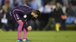 Bek Barcelona, Gerard Pique, tertunduk lesu usai timnya dikalahkan Celta Vigo. Kekalahan ini menjadi yang kedua bagi Barca musim ini di ajang La Liga. (AFP/Miguel Riopa)