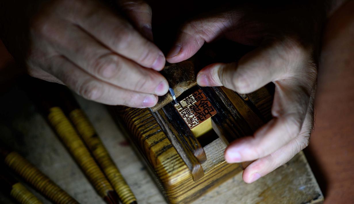 Pembuat stempel tinta tradisional Takahiro Makino, 44, mengukir karakter pada saputangan di Tokyo pada 9 Oktober 2020. Hanko atau stempel tinta tradisional digunakan untuk menandatangani segala sesuatu mulai dari tanda terima pengiriman hingga sertifikat pernikahan di Jepang. (Philip FONG/AFP)