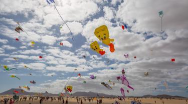 Orang-orang menerbangkan layang-layang selama Festival Layang-layang Internasional di Fuerteventura, kepulauan Canary, Spanyol, 10 November 2018. Festival diikuti 45 penerbang layang-layang profesional dan amatir dari delapan negara. (DESIREE MARTIN/AFP)