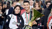 Cristiano Ronaldo bersama kekasihnya, Georgina Rodriguez, berpose dengan trofi Serie A di Stadion Allianz, Turin (19/5/2019). (AFP/Marco Bertorello)