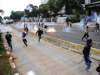 Pengunjuk rasa tolak UU Cipta Kerja bentrok dengan polisi di sekitar Patung Kuda, Jakarta Pusat, Selasa (13/10/2020). Gas air mata ditembakkan ke arah pendemo yang melakukan perlawanan dengan melempar batu dan pecahan kaca. (Liputan6.com/Faizal Fanani)