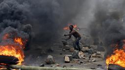 Pengunjuk rasa saat akan melemparkan batu kepada petugas polisi yang menghalangi mereka di Bujumbura, Burundi, (22/5/2015). Warga Asing yang berada di Burundi dipulangkan untuk menghindari konflik yang terjadi. (REUTERS/Goran Tomasevic)