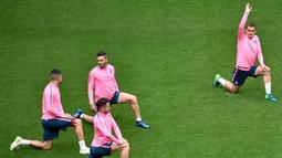 Para pemain Atletico Madrid melakukan pemanasan selama sesi latihan di stadion Parc OL di Decines-Charpieu (15/5). Atletico Madrid akan bertanding melawan wakil Prancis, Marseille pada babak final Liga Europa. (AFP Photo/Jean-Philippe Ksiazek)
